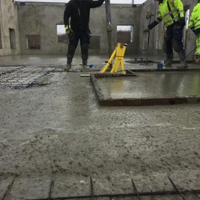 Kalle lägger ut betong och Anders kollar höjden